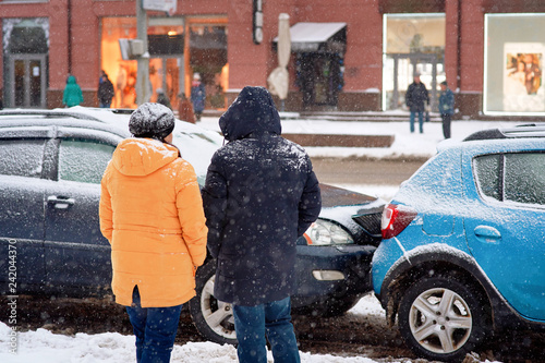 Drivers look at damaged cars after road accident in blizzard