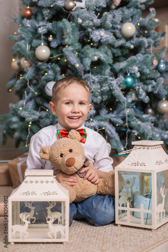 Fotografie, Obraz  Little boy under the Christmas tree with a toy