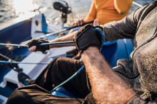 Close-up Of Male Hands In Gloves Pulling Rope Of Sailboat While Mooring Yacht And Sitting With Friends On Deck.