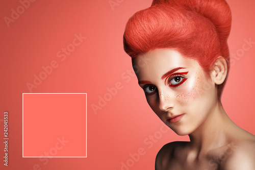 Fotografía  Beautiful woman with hair colored in color of 2019 Living Coral on blue backgrou