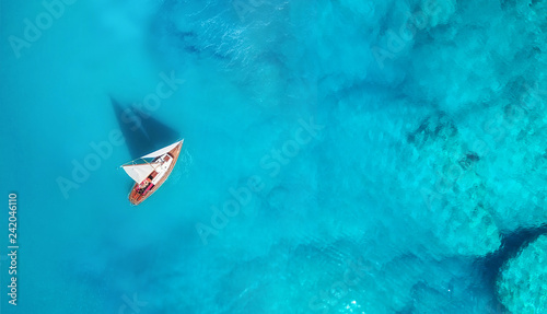 Yacht on the water surface from top view. Turquoise water background from top view. Summer seascape from air. Travel concept and idea