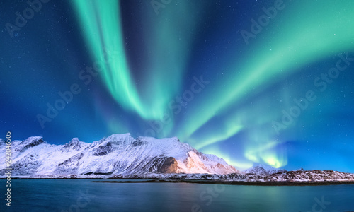 Aurora borealis on the Lofoten islands, Norway. Green northern lights above mountains and ocean shore. Night winter landscape with aurora and reflection on the water surface.