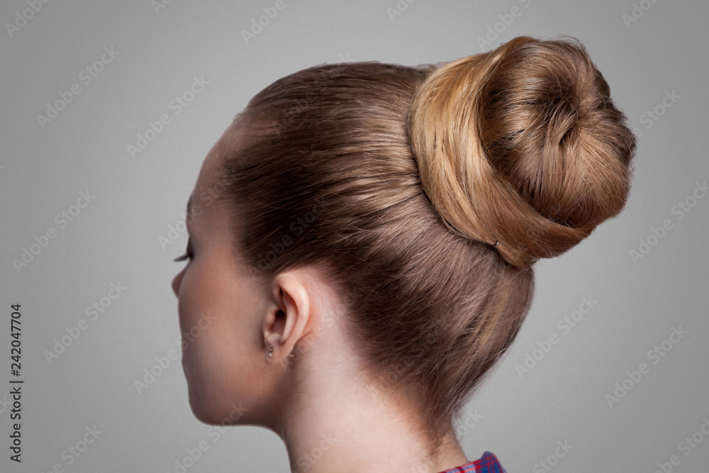 Fototapeta Profile side view closeup portrait of woman with creative elegant brown collected hairstyle, bun hair. indoor studio shot, isolated on grey background.