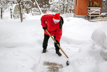 Man In Red Down Jacket And Red Hat Of Santa Claus Clears Snow In Backyard. Clears Snowdrifts On Path To Home. After Heavy Snowfall. Man Remove Snow With Big Plastic Shovel With Wooden Handle