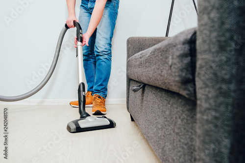 The man is vacuuming in the apartment Tablou Canvas
