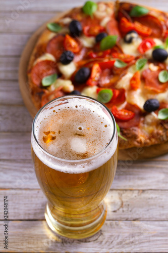 Foto op Canvas Bier / Cider Beer and pizza on wooden plate. Ale and snack. Vertical