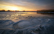Beautiful Winter landscape with frozen river, reeds and sunset sky. Composition of nature.