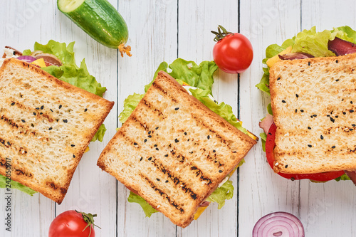 Foto Three sandwiches with ham, lettuce and fresh vegetables on a white background to