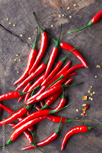 Photo Stands Hot chili peppers Close-up on red hot chili peppers on rustic wood, flat lay
