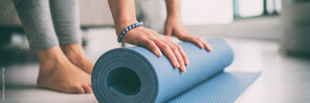 Fototapety, obrazy: Yoga at home active lifestyle woman rolling exercise mat in living room for morning meditation yoga banner background.