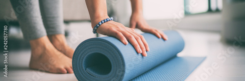 Spoed Foto op Canvas School de yoga Yoga at home active lifestyle woman rolling exercise mat in living room for morning meditation yoga banner background.