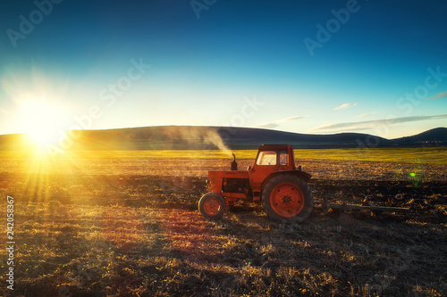 Fotografia  Tractor cultivating field at spring