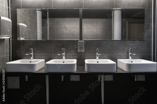 Fotografía  Faucets with washbasin in public restroom in grey colors
