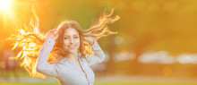 Girl With Long Hair On The Background Of The Sunset. Female Model In The Sun Smiling In The Park. Summer Time Scene.