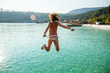 Young beautiful woman in bikini jumping into the turquoise sea, summer, vacation travel to tropical countries, adventure and freedom
