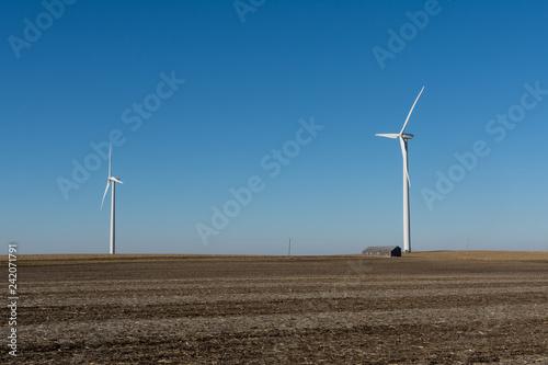 Fotografie, Obraz  Old wooden barn and windmill in open farmland.