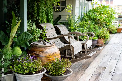 Obraz na płótnie Wooden rocking chairs in a cottage garden porch setting on wooden floor in vintage Thai botanical garden, with traditional Thai old water jar decoration