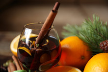 Still Life With Mulled Wine In A Glass With Two Sticks Of Cinnamon And Spices  With A Fir-tree Branch Close-up. Christmas Party.