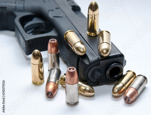 Fotografie, Obraz A black semiautomatic 9mm pistol with ten bullets on and around it, four full me