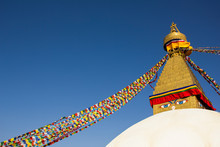 Tibetan Buddhist Stupa Boudhanath With Eyes And Multicolored Prayer Flags Against A Clean Blue Sky