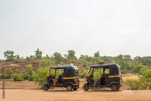 Fototapeta two black and yellow Indian motor rickshaws stand on an asphalt road against the