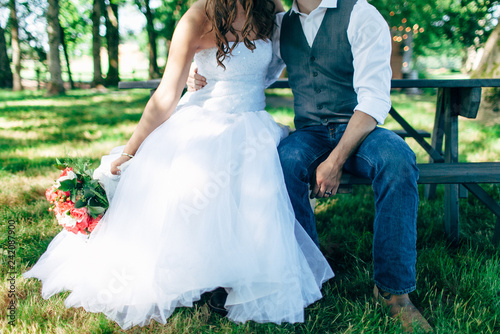 Fotografia, Obraz  country bride and groom in grass sitting on picnic table