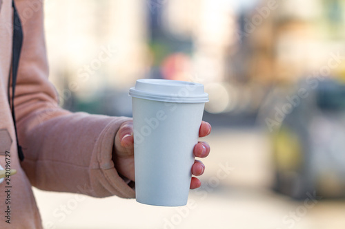 Poster Cafe Young woman in casual clothes holding paper coffee cup and enjoying the walk in the city in the morning on a sunny day. Coffee away and to go