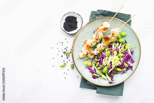 Chicken skewers with coleslaw with beans and pistachios. On a light background. Top view