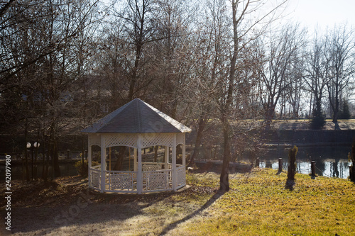 Green park in winter season with arbour or bower Fototapet