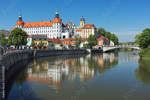 Naklejka premium Neuburg an der Donau, Niemcy. Zamek Neuburg, rezydencja książąt Palatynatu-Neuburga, odzwierciedlona w Dunaju w słoneczny dzień. Renesansowy zamek został zbudowany w latach 1530-1545.