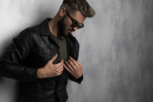 Portrait Of Man Buttoning Leather Jacket While Looking Down