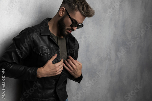 Fotografia  portrait of man buttoning leather jacket while looking down