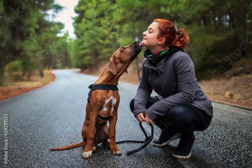 Portrait of happy teenage girl and Rhodesian ridgeback dog . Dog giving girl sweet kiss lick. Love animals love my pet