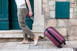 Girl traveler with suitcase arrives to authentic hotel or apartments in old town. Woman tourist opens ancient door. Concept of travel, vacation, solo female tourism, trip, adventure.