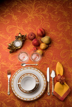 Table Service Organized With Orange Background, With Decoration Of Candles And Fruits