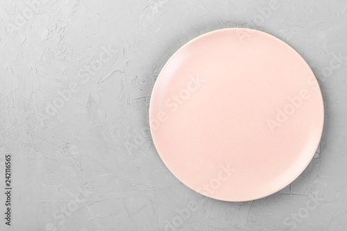 Top view of matte round empty rose plate on grey cement background space for you design