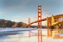 Golden Gate Bridge With Reflections On Water At Sunset Low Tide Time.