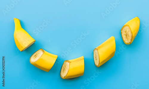 Cut banana slices on blue background flat lay top view