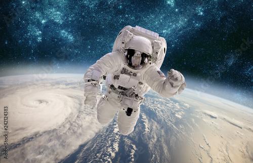 Fototapeta premium Astronauta w kosmosie na tle planety Ziemia. Tajfun nad Ziemią.