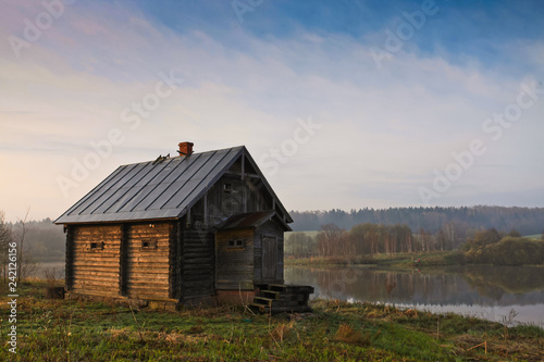 Carta da parati Ancient rural house in the early spring on the shore of the lake