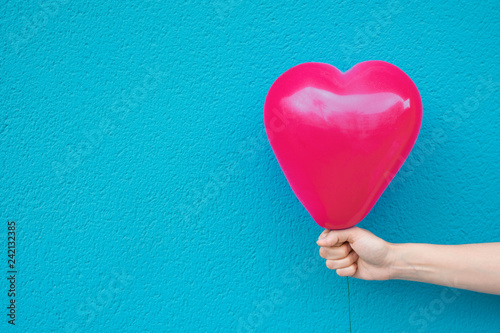 Photo  Young caucasian woman girl holds in stretched hand bright pink heart shape air balloon on turquoise painted wall background