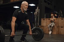 Indoor Shot Of Handsome Unshaven Male Seventy Year Old Male Athlete In Stylish Sports Clothes Enjoying Powerlifting Training, Holding Barbell, Doing Squats, Smiling Confidently. Selective Focus
