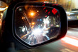 Mirror view of car at night. Bokeh image of lighting in the glass. Fast of other cars with red light. Reflection of the red speedometer curtain.