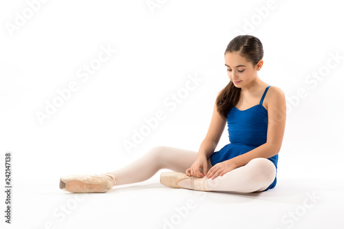 Fotografia  Seated ballerina tying the laces on her shoes