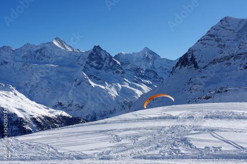 Parapente disparaissant derrière une piste de ski