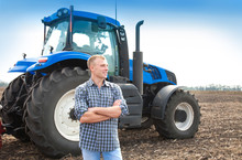 Young Attractive Man Near A Tractor. Concept Of Agriculture.