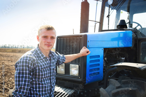 Young attractive man near a tractor. Concept of agriculture. Wallpaper Mural