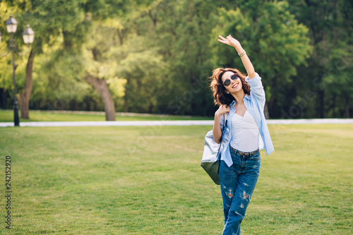 Cute brunette girl with short hair in sunglasses  posing in park Canvas Print