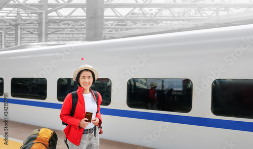 Fotografia  Solo travelling , middle aged asian female tourist travel with high-speed trai