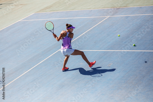 Female tennis player hits the ball with backhand.